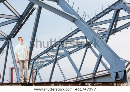 young men on background old metal bridge