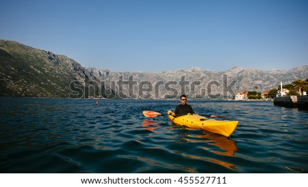 Young men paddle a kayak on the sea in Boka bay, Montenegro - stock photo