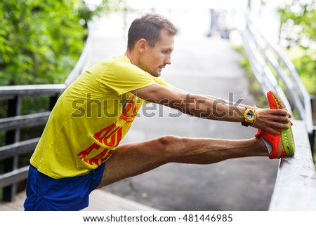 Young men performs stretching before jogging