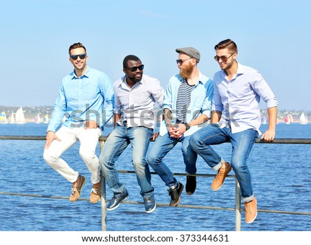 Young men relaxing on the riverside - stock photo