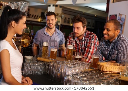 Young men sitting at counter in pub, drinking beer and flirting with attractive bartender.