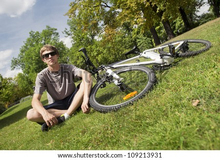 Young men sitting next to the bike