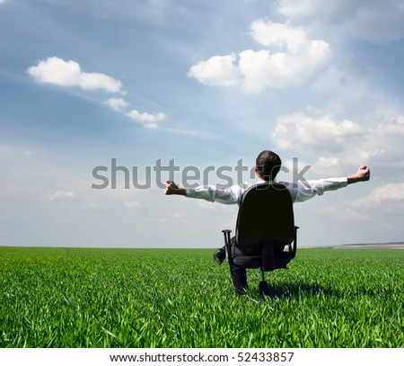 Young men sitting on chair in green meadow - stock photo