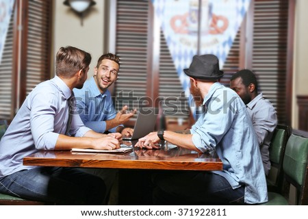 Young men talking in cafe - stock photo