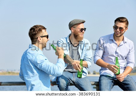 Young men talking on the riverside - stock photo