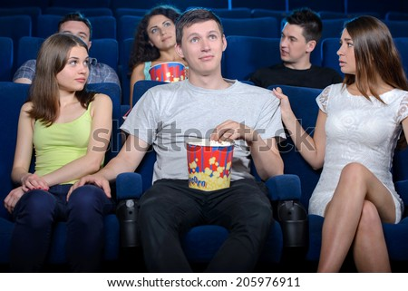 Young men touching the leg of the beautiful stranger women while sitting with his girlfriend at the cinema