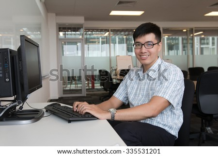 Young men types computer in his office