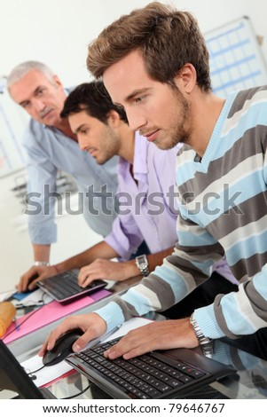 Young men using computers - stock photo