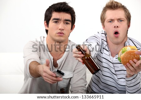 Young men watching TV - stock photo