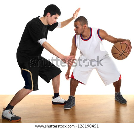 Young men - white and mulatto - playing basketball on wooden floor. - stock photo