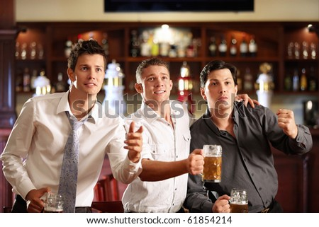 Young men with a beer watching the match in the bar - stock photo