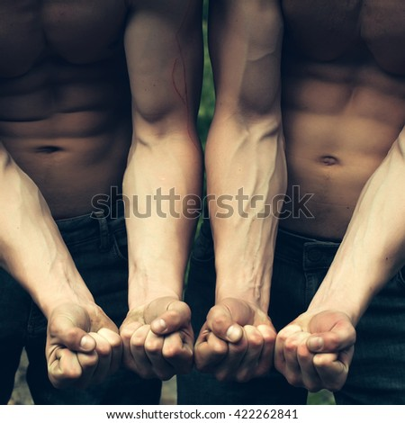Young men with muscular bodies showing strong hands in fists sunny day outdoor - stock photo