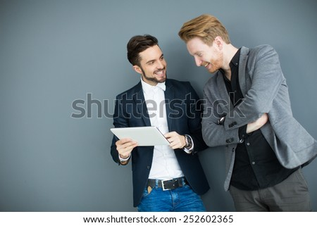 Young men with tablet in the office - stock photo