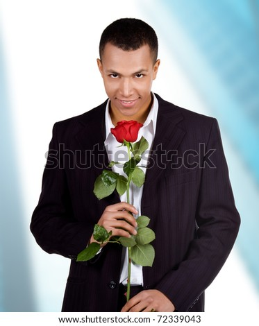 Young men with the red rose on blue background - stock photo