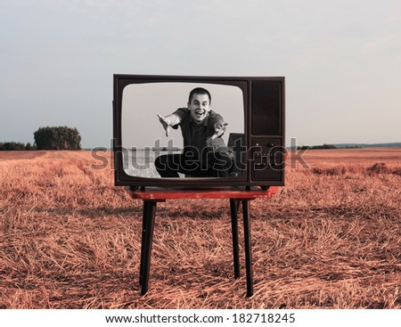 young men with TV in summer field