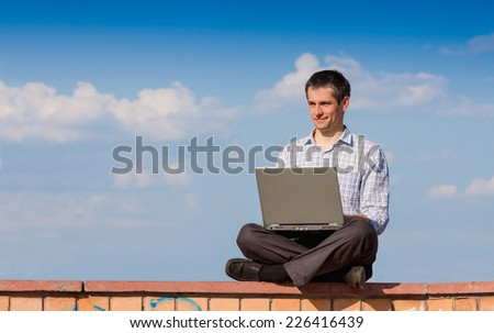 Young men working on laptop outdoor  - stock photo