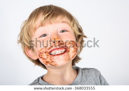 Young messy boy with chocolate on his face - stock photo