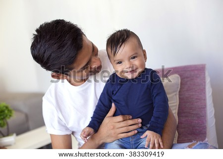 Young mexican father takes care of his six month baby boy - stock photo
