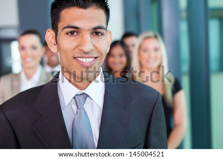 young middle eastern businessman with group of businesspeople on background - stock photo