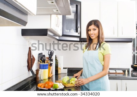 young middle eastern woman cooking in kitchen - stock photo