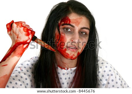 Young Middle Eastern woman covered in blood with knife. - stock photo
