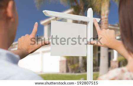 Young Military Couple Framing Their Hands Around Blank Real Estate Sign and House. - stock photo