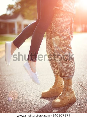 Young military couple kissing each other, homecoming concept, warm orange toning applied - stock photo
