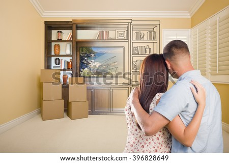 Young Military Couple Looking At Drawing of Entertainment Unit In Room With Moving Boxes. - stock photo