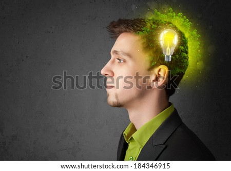 Young mind thinking of green eco energy with lightbulb on grungy background - stock photo