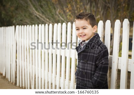 Young Mixed Race Boy Waiting For School Bus Along Fence Outside. - stock photo