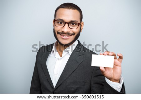 Young mixed race businessman with beard and suit standing on grey background. Young man smiling and holding visit card