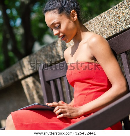 Young mixed race businesswoman portrait outdoors in London while using tablet sit on a bench in a park. Filtered image.