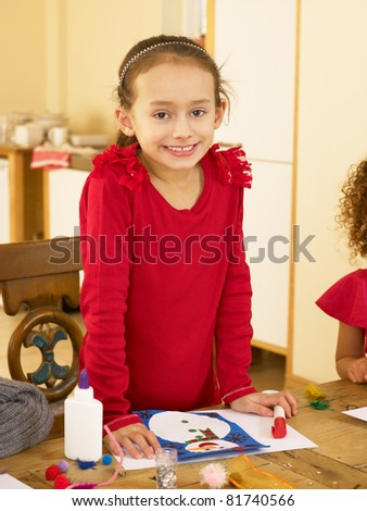 Young mixed race child making Christmas cards - stock photo