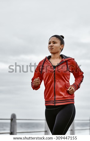 young mixed race female busy taking a jog along the sea side on the promenade, maintaining her active life style is essential - stock photo