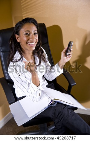 Young mixed-race Hispanic African-American female office worker with notebook and mobile phone