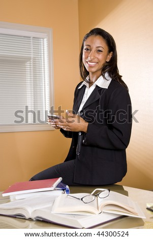 Young mixed-race Hispanic African-American woman with books and mobile phone - stock photo