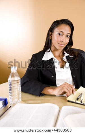 Young mixed-race Hispanic and African-American woman reading and taking notes - stock photo