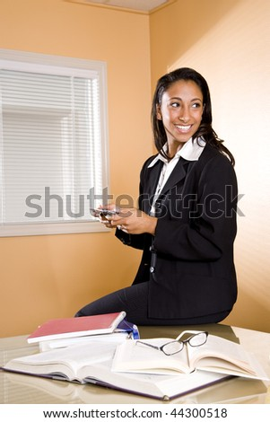 Young mixed-race Hispanic and African-American woman texting while studying - stock photo