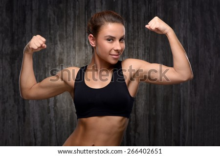 Young mixed race sporty woman wearing black tracksuit for training. She looking at camera and demonstrating her biceps. Fitness concept - stock photo