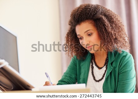 Young mixed race student with an afro hairstyle working and designing at her desk  - stock photo