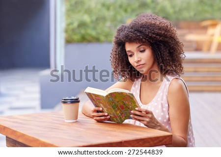 Young mixed race woman sitting a table outdoors with her takeaway coffee reading a book  - stock photo