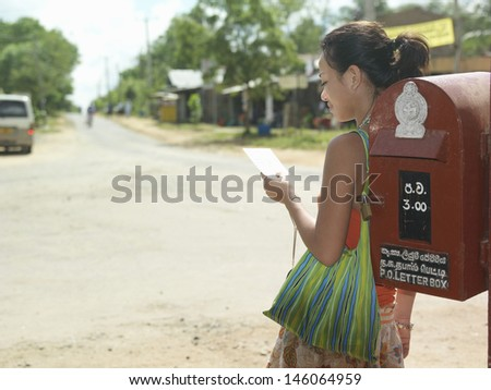 Young mixed race woman standing by mailbox and reading postcard - stock photo