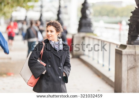 Young mixed race woman walking  in London on the Queens Walk next to Thames river. She is wearing a black coat and a scarf. Big Ben and Parliament on background. Tourism and lifestyle concepts.