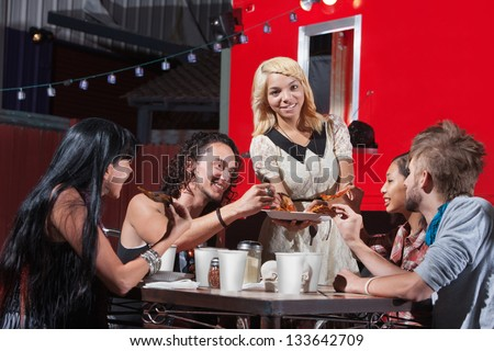 Young mixed woman sharing pizza with friends at cafe