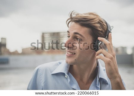 young model handsome blonde man with music headphones in the city