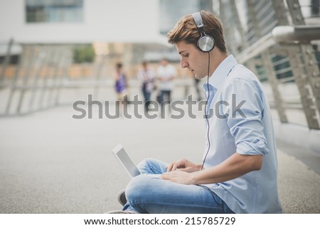 young model handsome blonde man with notebook and headphones in the city - stock photo