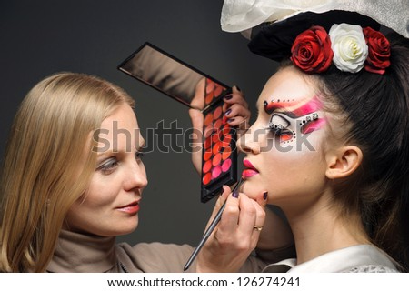 Young model having her makeup done before her shoot, make up master - stock photo