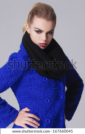 young model in a blue coat posing-gray background - stock photo