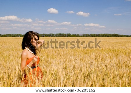 young model in dress in the field of wheat