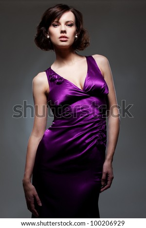 young model in violet dress over dark background